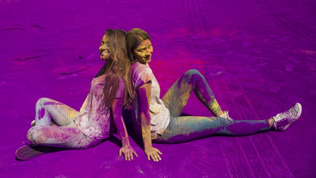 smiling-young-women-sitting-back-back-sitting-holi-color-indian-parents-talks