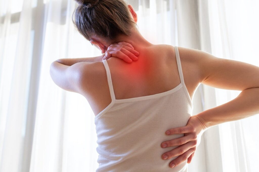 Body pain Young woman suffering from neck pain and backache, stretching the muscles.